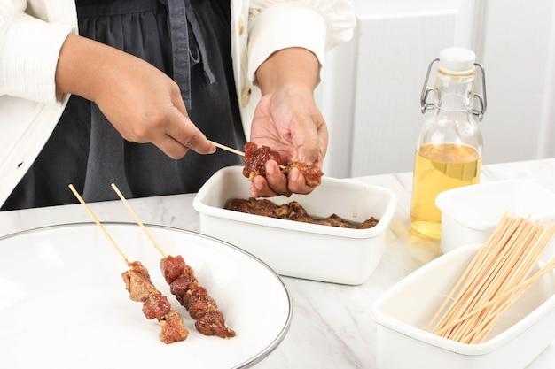 Preparando satay de cordeiro caseiro (sate kambing) para o menu idul adha. sate kambing é comida de rua popular na indonésia. conceito de cozinha limpa