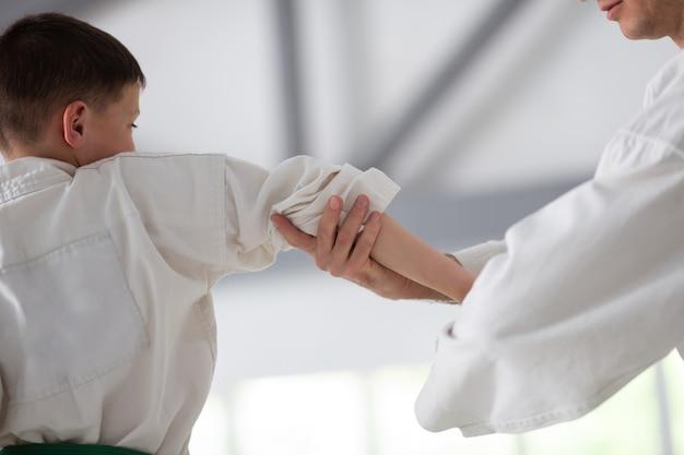 Preparando-se para a competição. garoto ativo de cabelos escuros se preparando para uma competição de aikido com treinador