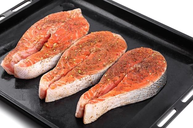 Preparando-se para cozinhar bifes de peixe cru vermelho com especiarias na bandeja preta