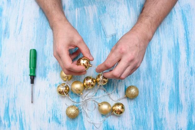 Preparando-se para o ano novo. reparo de uma guirlanda elétrica de abeto. nas mãos de um eletricista, clippers e pinça