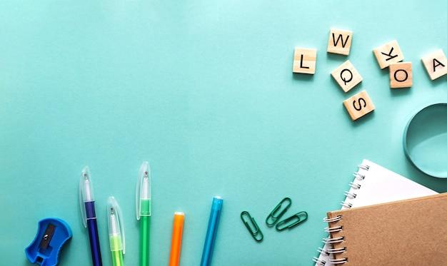Preparando-se para o conceito leigo do ano letivo com papel de carta azul da vista superior da mesa de volta ao conceito da escola.