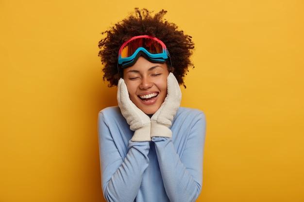 Preparando-se para o inverno. mulher jovem e alegre, cacheada, vestindo snowboard, mantém as duas mãos no rosto, usa luvas quentes, relembra agradável momento de férias