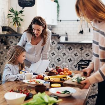 Preparando-se para o jantar em família, as mulheres põem a mesa, enquanto a menina aprende as lições.