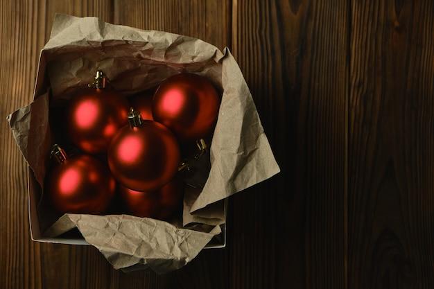 Preparando-se para o natal. decorações para a árvore de natal. bolas vermelhas de natal em uma caixa sobre uma mesa de madeira
