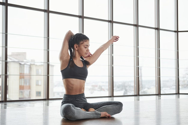 Preparando-se para os exercícios difíceis. jovem bonito relaxado senta-se no chão no ginásio com grandes janelas