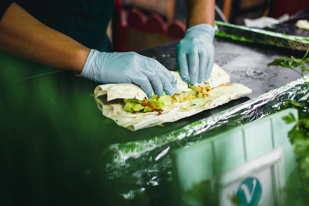 Preparando um envoltório saudável com carne e legumes para viagem