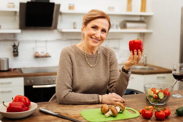 Preparando uma refeição leve. mulher alegre e bonita sendo positiva enquanto se inclina sobre uma mesa de madeira e mostra o pimentão vermelho