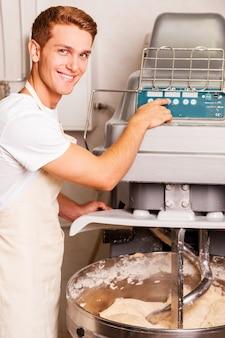 Preparar massa para pastelaria. jovem confiante de avental apertando o botão da máquina de mistura de massa e sorrindo
