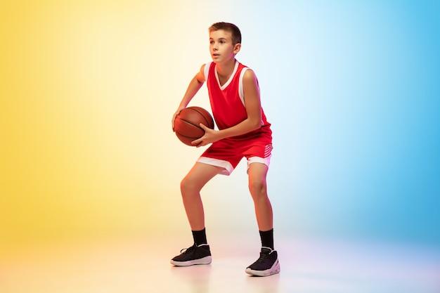 Preparar. retrato de jovem jogador de basquete de uniforme em parede gradiente