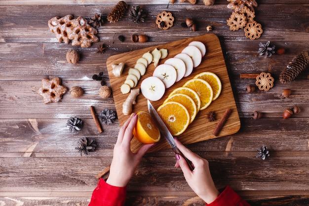 Preparativos de ano novo e natal. olhe de cima para mulher cortando frutas f