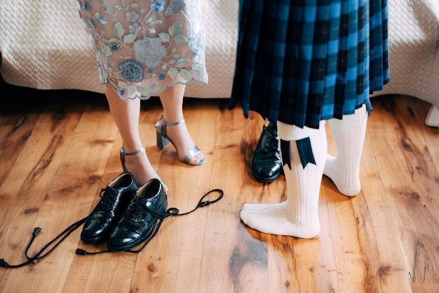 Preparativos para o casamento escocês, homem de kilt ao lado de mulher com saia e sapatos de salto alto