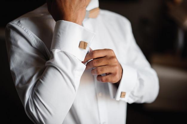 Prepare a preparação da manhã. noivo se vestindo com uma camisa de casamento com gravata borboleta de madeira