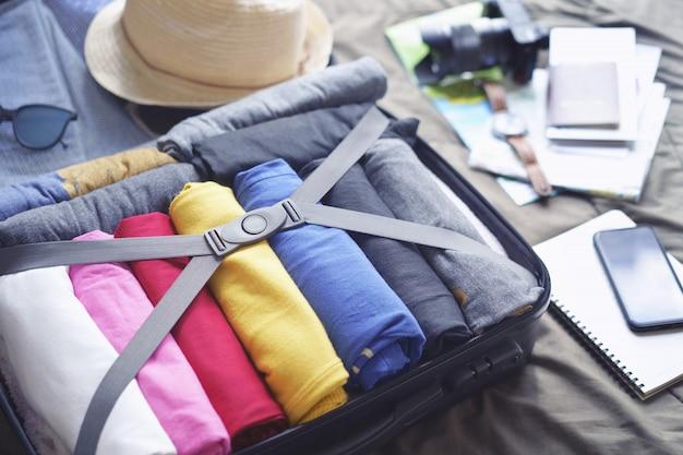 Prepare os acessórios para a viagem e viaje para uma longa viagem de fim de semana, embalando roupas em mala de viagem na cama.