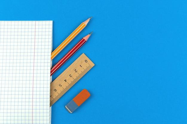 Prepare-se para a composição do conceito dos primeiros dias letivos, plano de fundo azul plano com caderno, lápis, régua de madeira e borracha, cópia da foto da vista superior do espaço