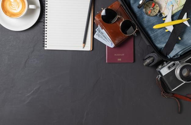 Prepare uma mala, câmera vintage, caderno, passaporte, mapa e café quente no chão de ladrilhos pretos e copie o espaço. conceito de viagens