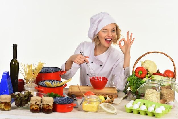 Preparo da comida. conceito de cozinha profissional. mulher alegre cozinhando na cozinha. feminino? hef sentado à mesa com produtos, mistura em tigela vermelha mostra gesto ok. copie o espaço para anunciar restaurante.