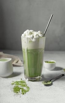 Preparou chá matcha em um copo transparente. uma deliciosa bebida feita de pó de chá verde japonês. posição vertical