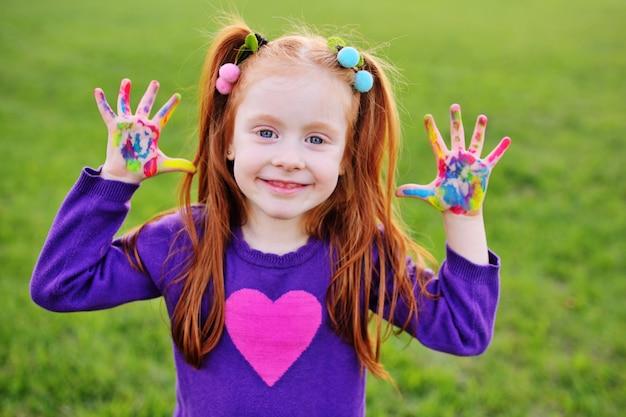Preschooler garota ruiva mostra as palmas das mãos manchadas com tintas multicoloridas