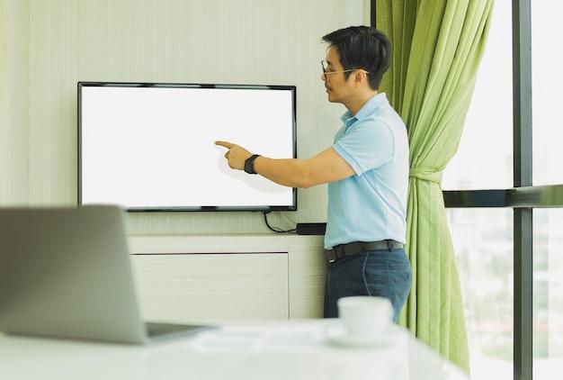 Presença de empresário na sala de conferências com a mão apontando para a tela