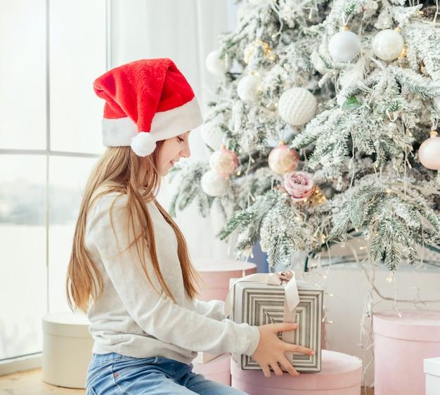 Presente aberto de adolescente perto de árvore de natal
