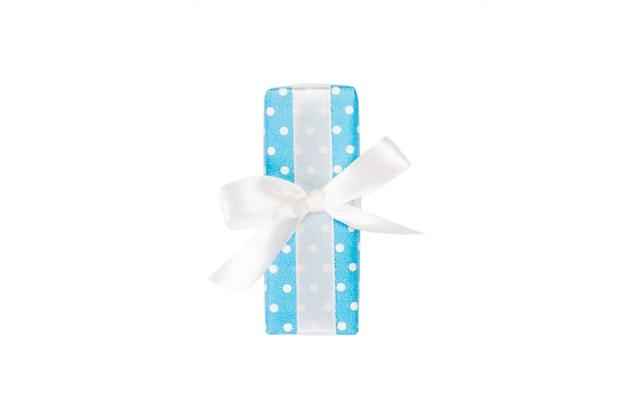 Presente artesanal de natal ou outro feriado em papel azul com fita branca. isolado no branco