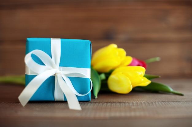 Presente azul com tulipas. férias de concepção, 8 de março, aniversário, mo
