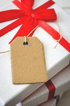 Presente branca com etiqueta na maquete da mesa de madeira