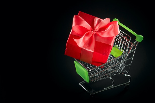 Presente caixa de presente em embalagens festivas com laço de cetim no carrinho de compras.