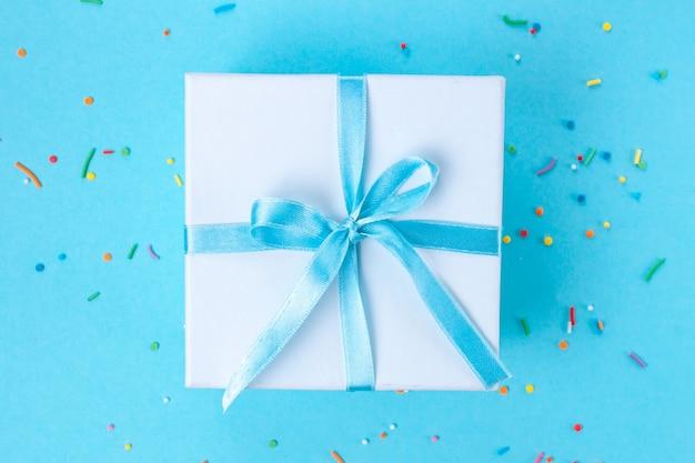 Presente, caixinha amarrada com uma fita azul de cetim. conceito de presente.
