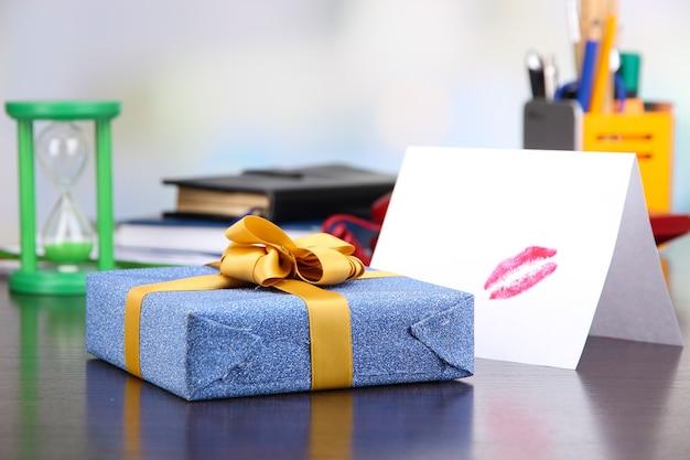 Presente com cartão para um ente querido na área de trabalho no fundo da sala