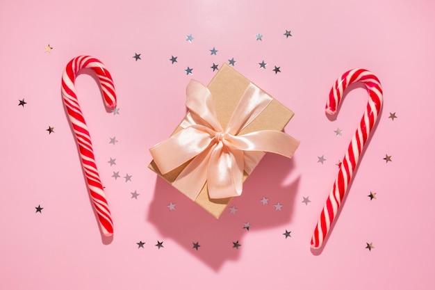 Presente com doces vermelhos de natal e estrelas de confetes derrama sobre um fundo rosa pastel, vista superior. postura plana. ano novo de férias, conceito de atmosfera de celebração