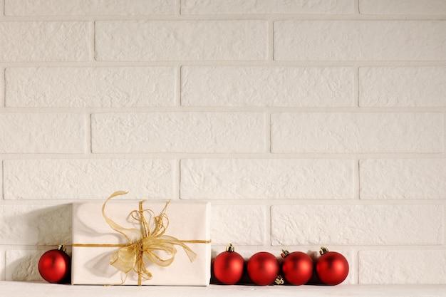 Presente com enfeites vermelhos em fundo de tijolos brancos