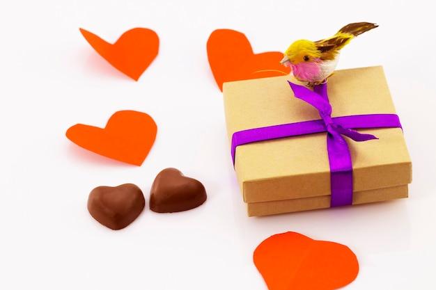 Presente com fita roxa e doces em forma de coração em fundo branco dia dos namorados