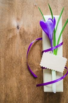 Presente com flor fresca e nota em branco.