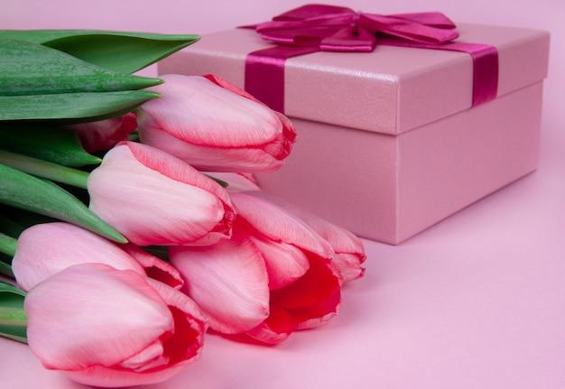 Presente com flores tulipas em um fundo rosa no dia dos namorados, no dia das mães