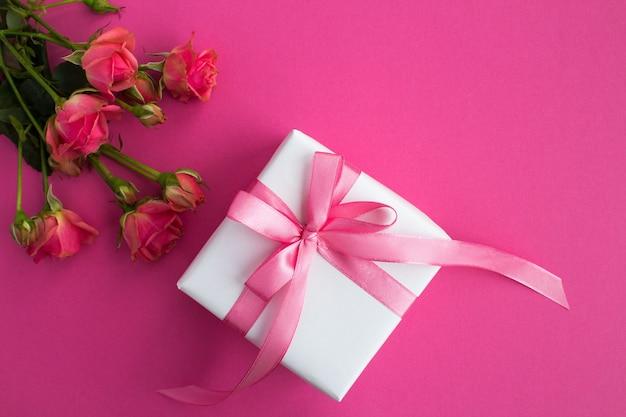 Presente com laço rosa e rosas cor de rosa no fundo rosa escuro. vista superior. espaço de cópia.