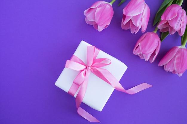 Presente com laço rosa e tulipas cor de rosa na superfície violeta.