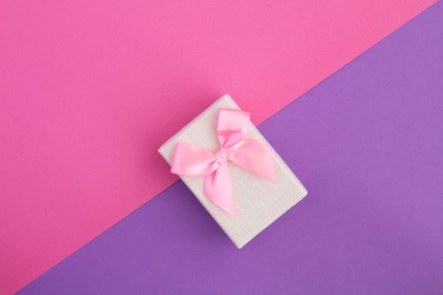 Presente com laço rosa na mesa colorida. vista superior. copie o espaço.