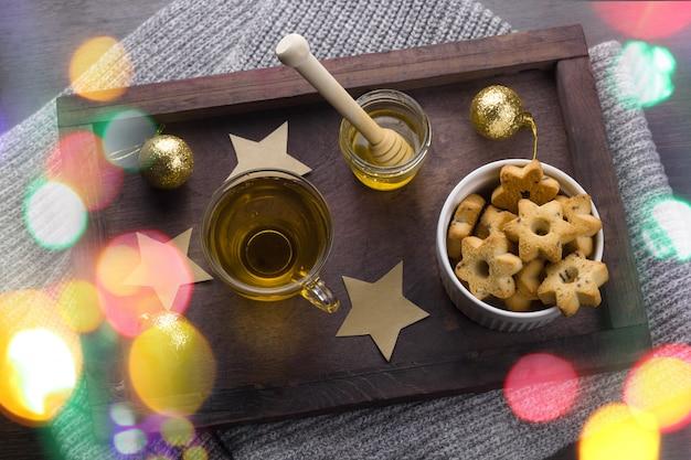 Presente com laço vermelho, biscoitos em forma de estrelas, xícara de chá