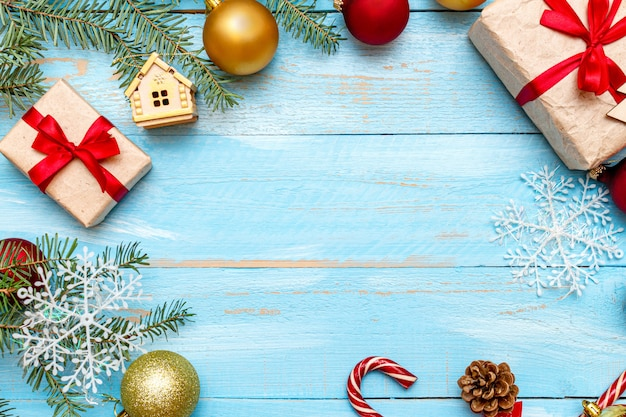 Presente com laço vermelho e decoração de natal no fundo de madeira pintado de azul