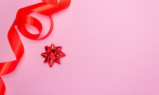 Presente com laço vermelho em um fundo rosa e fita de cetim vermelha na lateral