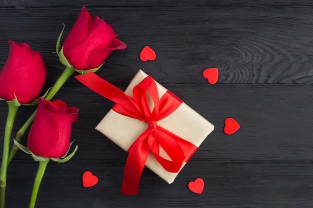 Presente com laço vermelho, rosas vermelhas e corações vermelhos na madeira preta