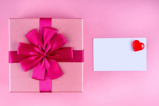 Presente com nota de amor com coração vermelho em simulação de fundo rosa, copyspace