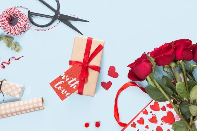 Presente com tag perto de tesoura, rosas e bobina de torções