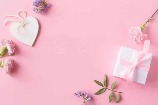 Presente, coração branco de madeira e flores sobre fundo rosa