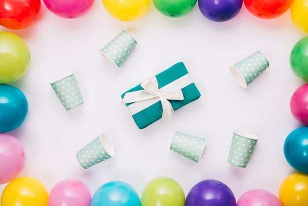 Presente de aniversário cercado com copo descartável dentro da borda de balões no fundo branco