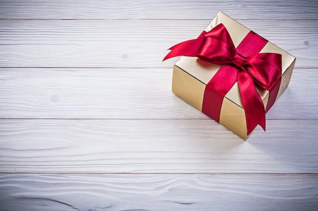 Presente de aniversário com fita de cetim vermelha no conceito de férias de tábua de madeira