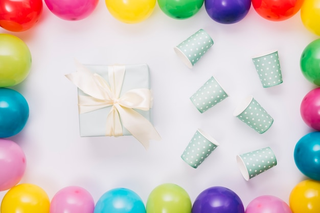 Presente de aniversário e copo descartável dentro da borda de balões no fundo branco