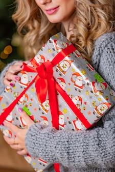 Presente de ano novo com uma fotos de papai noel envolto em uma fita vermelha está nas mãos de uma mulher. fechar-se
