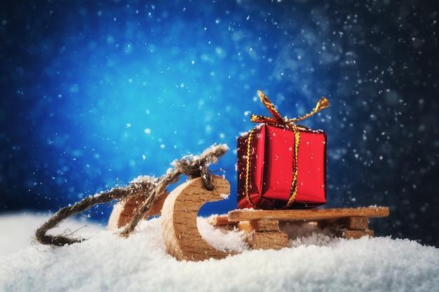 Presente de ano novo do papai noel em um trenó em um monte de neve